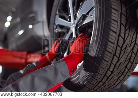 Unrecognizable Mechanic In Uniform And Gloves Detaching Wheel From Vehicle During Work In Profession