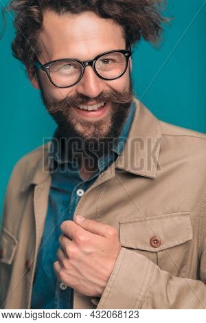 happy casual young man with glasses holding jacket, arranging and smiling on blue background in studio, portrait