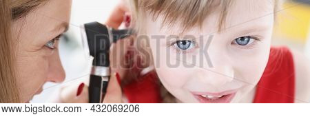Female Doctor Conducts Examination Of Ear Of Little Girl