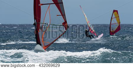 Windsurfers Surfing The Wind On Waves In Ocean Sea