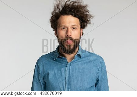 goofy young bearded man in denim shirt sticking out tongue and making silly faces on grey background in studio