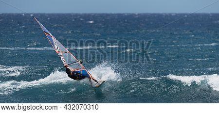 Windsurfer Surfing The Wind On Waves In Ocean Sea