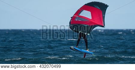 A Man Is Wing Foiling Using Handheld Inflatable Wings And Hydrofoil Surfboards In A Blue Ocean, Ride