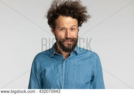 young casual man in denim shirt with curly hair making funny faces and grimacing on grey background in studio