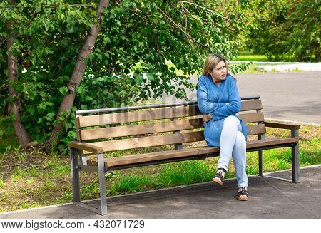 Cool Day. The Woman On The Bench Is Wrapping Herself In A Warm Cardigan. The Woman Froze. Coldly. On
