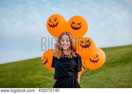 Young Teen Girl In Black Clothes Holding Bunch Of Halloween Balloons On Green Hill. Copy Space. Holi
