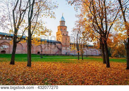 Autumn in the city. Veliky Novgorod, Russia, autumn Kremlin park in sunset light. Kokui tower of Veliky Novgorod Kremlin and beautiful autumn park with orange fallen leaves