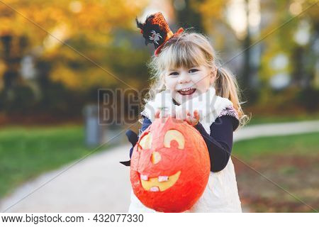 Little Toddler Girl Dressed As A Witch Trick Or Treating On Halloween. Happy Child Outdoors, With Or