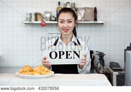 Young Asian Shopkeeper With A Smile Holds An Open Sign In Front Of A Coffee Shop Counter. Morning At