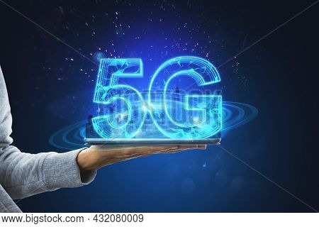 Hand Holding Tablet With Creative Glowing 5g Hologram On Blue Background. Internet Speed, Connection
