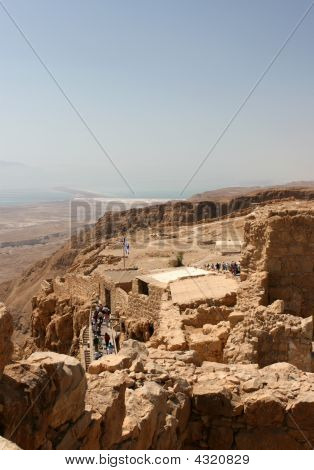 Tourist climb over the ruins of the mountain top fortress of Masasda Israel built close the Dead Sea by King Herod between 37 and 31 BCE. poster