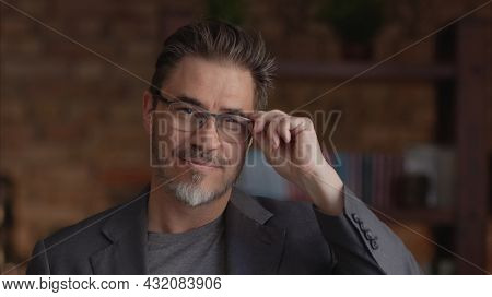 Confident businessman smiling in glasses. Portrait of mature age, middle age, mid adult man in 50s, happy confident smile. Copyspace.