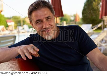 Portrait of mature age, middle age, mid adult man in 50s, happy confident smile. Smoking cigar.