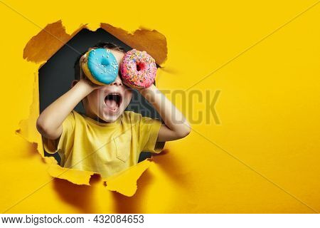 Happy cute boy is having fun played with donuts on Yellow background wall. Bright photo of a boy. Colored donuts
