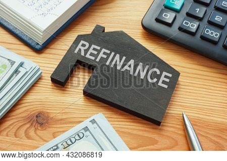 Refinance Home Mortgage Concept. Model Of House On The Table.