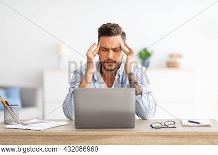 Deadline Stress Concept. Exhausted Man Tired After Working On Laptop, Massaging Temples, Sitting At