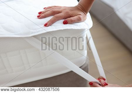 Woman Puts Blanket Or Mattress Topper On Bed Closeup