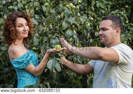 Attractive Woman Holding An Apple On Palm And Offers It To Man Of Middle Eastern Appearance. Man Res
