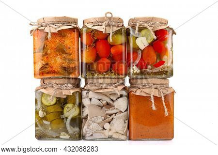 Preserved vegetables in glass jars with fresh vegetables isolated on white background