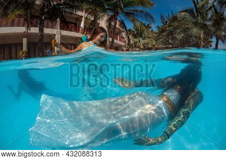 Group of happy women drinking in pool party - Young  people having fun in swimming pool under water