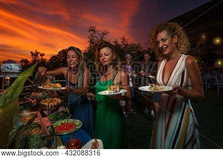 Group of friends having furshet in the backyard at summer sunset. Young women are putting food on a plate