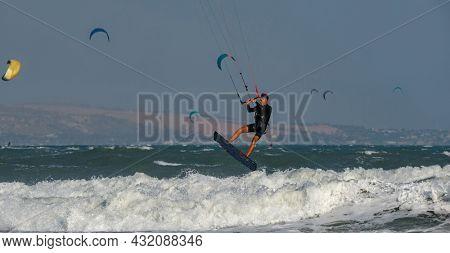 Kitesurfing on the waves of the South China sea, Vietnam. Kitesurfing, Kiteboarding action photos Kitesurfer In action