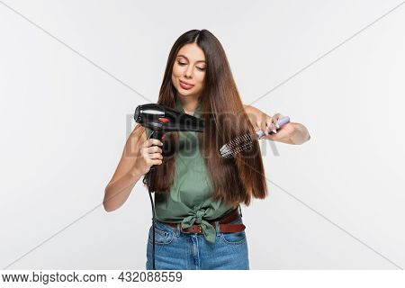Young Woman With Shiny Hair Styling Hair With Hair Dryer And Hair Brush Isolated On Grey