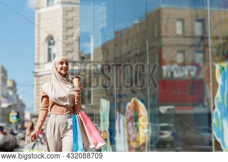 Surprised Happy Young Beautiful Arabian Female In Hijab With Colored Shopping Bags And Drink