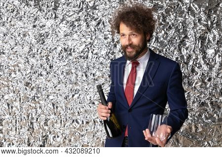 portrait of happy young man in navy blue suit holding champagne bottle and glasses, looking up and side and posing in front of tinfoil background in studio