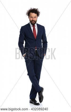 handsome businessman crossing his legs and holding his arms in pockets against white background