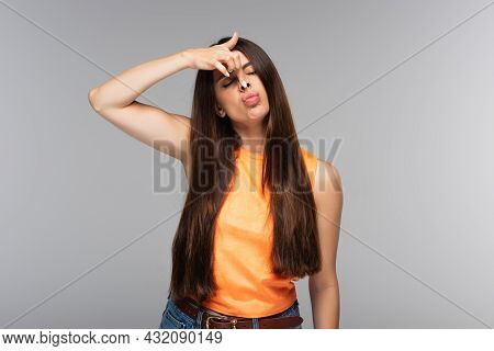 Young Woman Pouting Lips And Grimacing Isolated On Grey