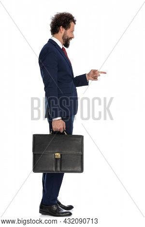 side view of a handsome businessman pointing to the side and looking at the camera