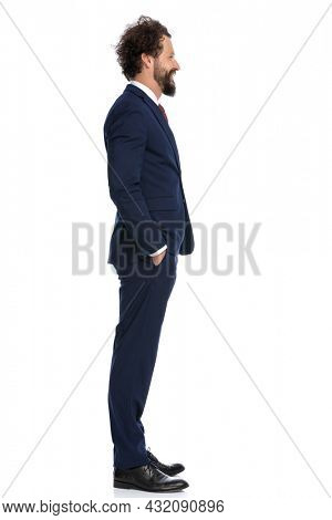 side view of a businessman waiting in line with his arms in pockets against white background