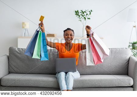 Happy Black Lady Holding Shopper Bags And Credit Card, Using Laptop To Place Online Order While Sitt