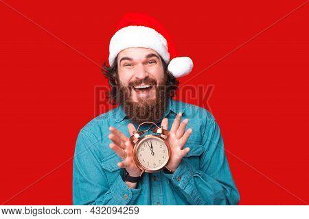 Happy Bearded Man In Santa Claus Hat Holding Alarm Clock At 12 O Clock