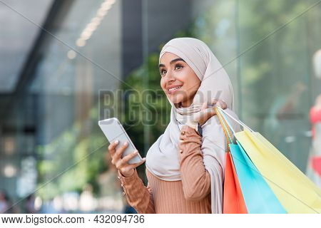 Smiling Pretty Millennial Arabian Lady In Hijab Enjoys Online Shopping With Bags, Surfing On Phone