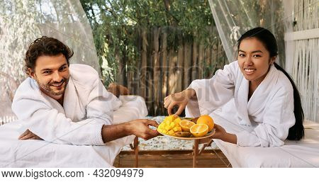 Couple In Love While Romantic Weekend . Handsome Man With Asian Girlfriend Eating Exotic Fruits At S
