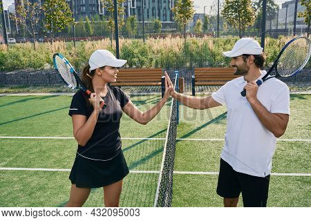 Tennis Players Giving Handshakes Near Tennis Net Before Game. Man And Woman Playing Tennis One To On