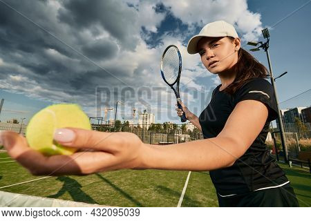 Female Tennis Player With Tennis Racket And Ball In Action And Motion During Tennis Match