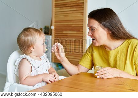 Smiling Mother Feeding Baby With Spoon. Child Sitting On High Chair While Mum Giving Food To Toddler