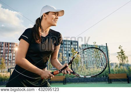 Brunette Female Tennis Player With Tennis Racket While Tennis Game In Motion