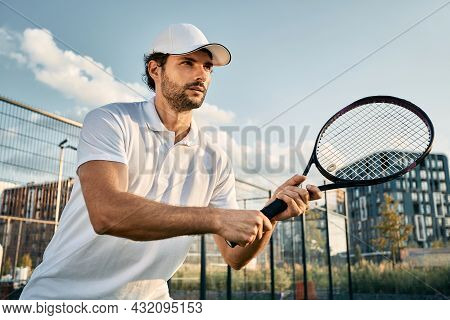 Handsome Tennis Player With Tennis Racket While Tennis Match In Motion