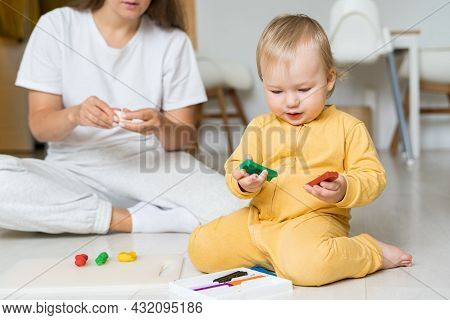 Child Hands Playing With Colorful Playdough. Moulding From Plasticine On Floor. Playing With Clay At
