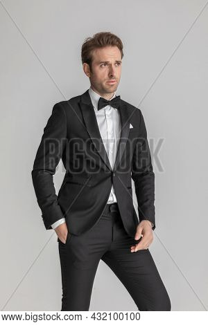 sexy businessman holding a hand in pocket and the other loose while looking away in a fashion pose