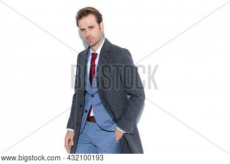 attractive businessman is posing with one hand in pocket and wearing a coat in a fashion pose