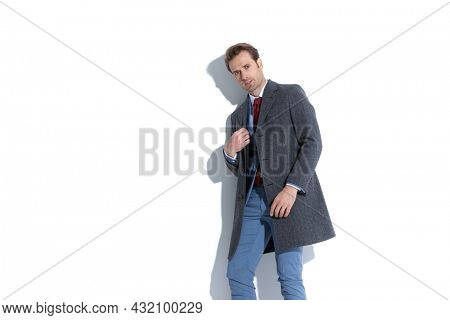 side view of an attractive businessman arranging his coat and posing with attitude on white background