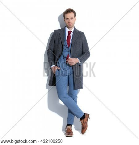cool businessman crossing his legs, holding one hand in pocket and arranging his coat on white background