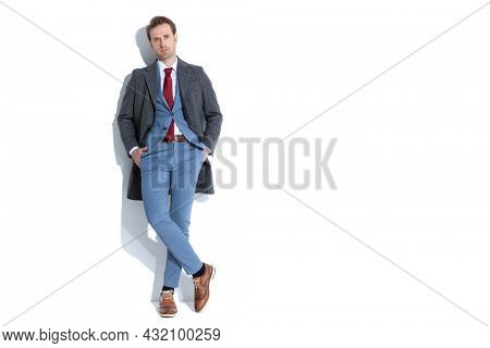 sexy businessman holding his hands in pockets and posing with his legs crossed on white background