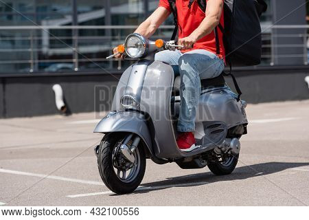 Cropped View Of Deliveryman In Red T-shirt And Thermo Backpack Driving Scooter