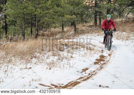 senior male cyclist riding a fat mountain in winter scenery of Horsetooth Mountain in Colorado